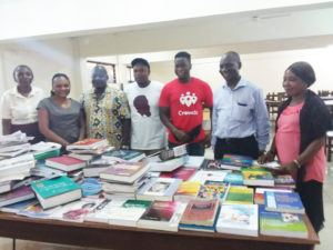 Maila and Sheku standing with faculty of College of Medicine and Allied Health Sciences with their donation of over 250 medical and nursing textbooks copy